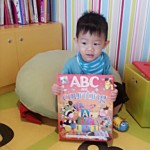 Little boy holding on a ABC big book.