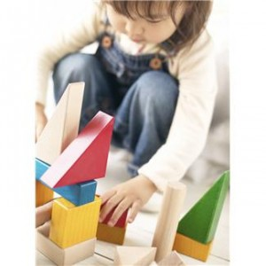 A toddler girl building with blocks.