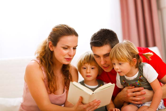 Parents reading to their two children.