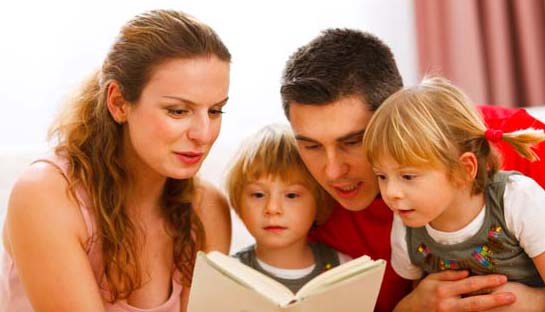 Parents reading to their two young children.