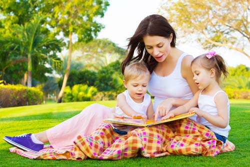 Young brunette mother reading to two young kids on a green field.