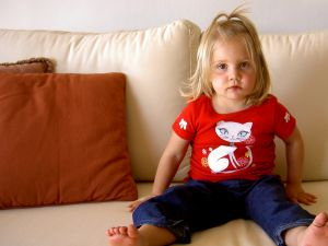 A cute little girl sitting on a couch.