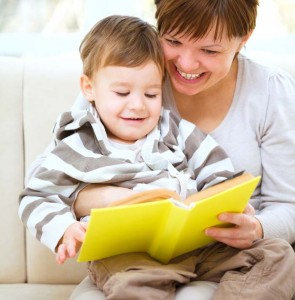 A mother reading a yellow book with her baby boy.