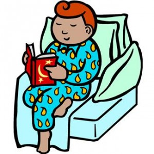 Little boy sitting on a comfy sofa and reading.