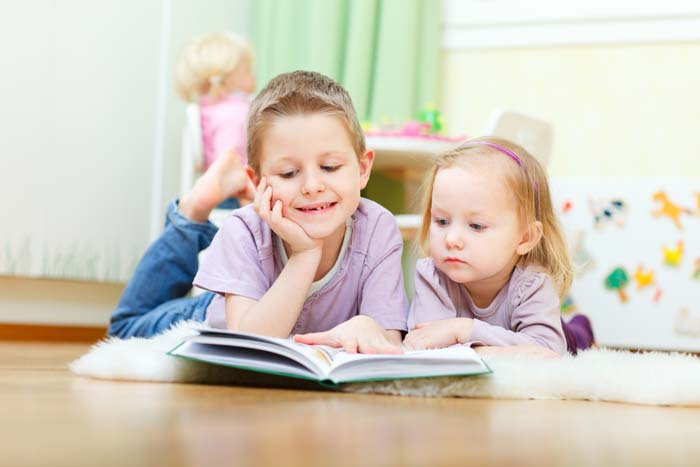 Brother and sister reading a book together.