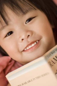 A young girl holding onto an opened book.