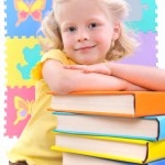 A girl preschooler standing next to a stack of books.