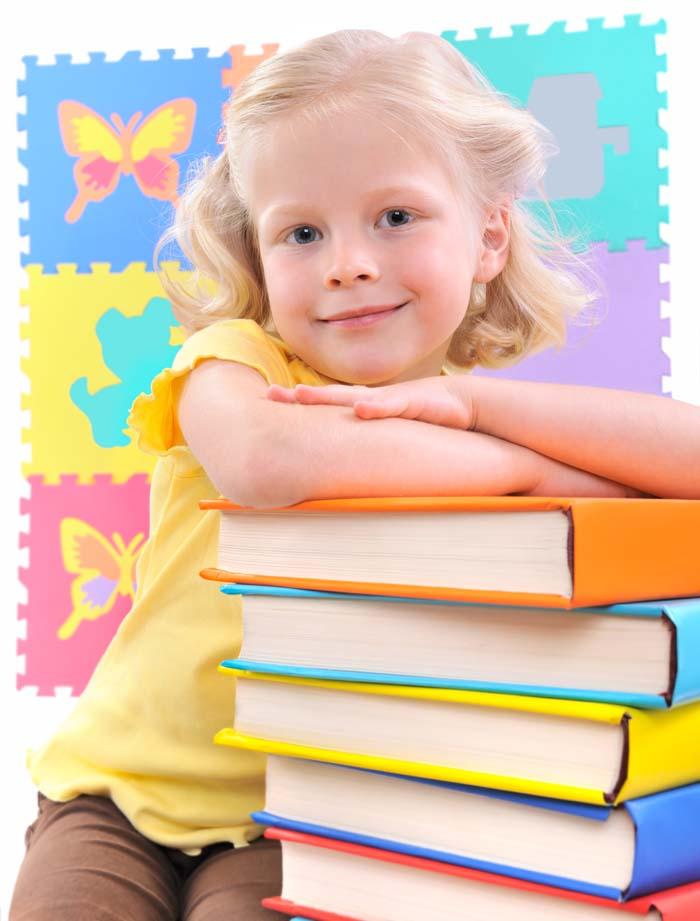 A girl preschooler standing next to a stack of books.