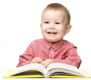Toddler and reading. Cute boy in red checkered shirt reading a book.