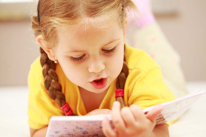 Little girl in yellow top reading a book, early childhood reader.