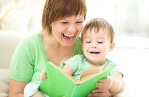 Mother reading a story book to her toddler son.