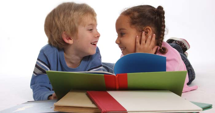 A boy and a gilr laughing among a pile of books.