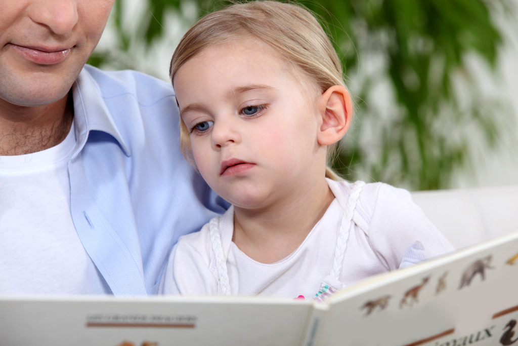 A girl reading a book together with her father.