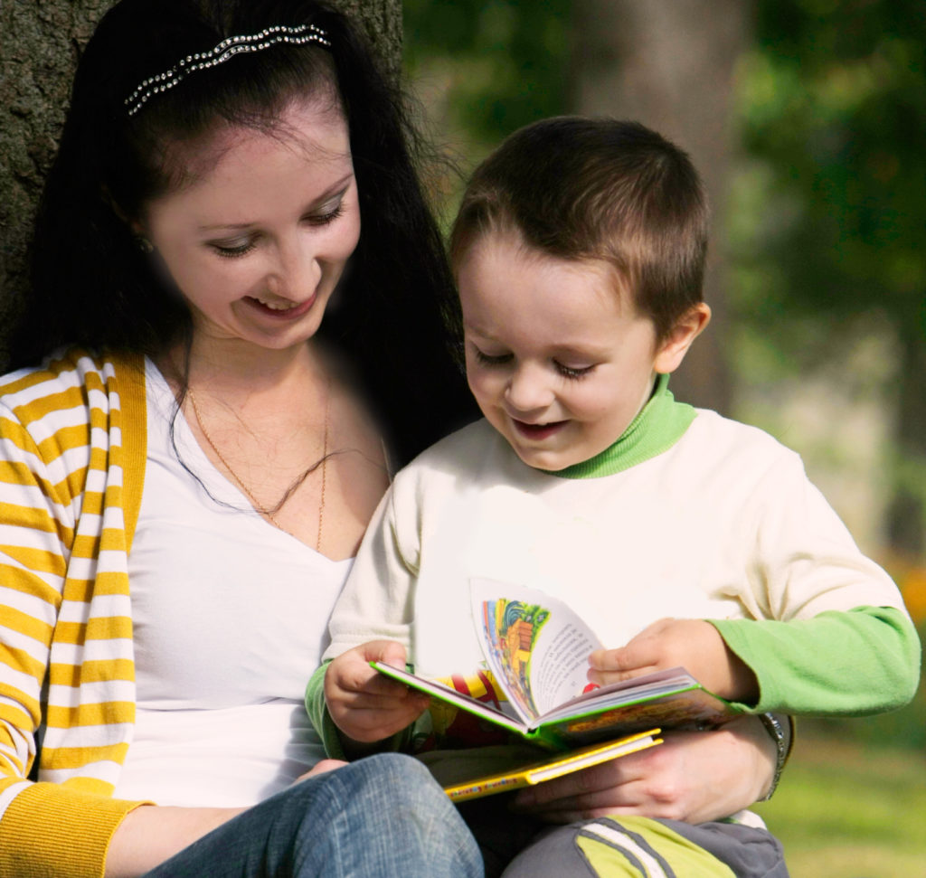 Mother and young son reading a book together. Tips on helping your child to read faster.